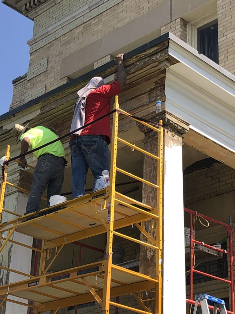 painters repair woodwork on west porch